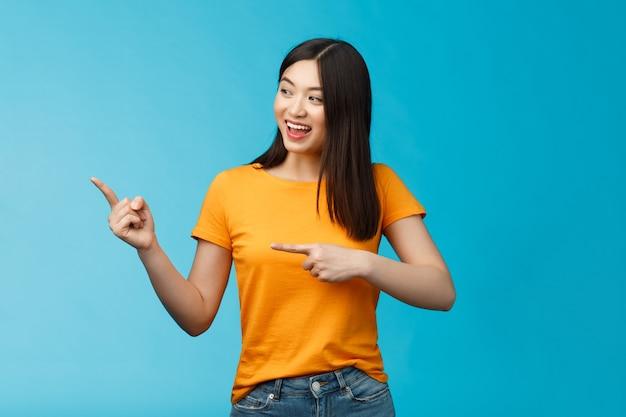 Vriendelijk enthousiast aziatisch meisje dat nieuwsgierig zijwaarts kijkt, naar links interessant object wijst, vrolijk grijnzend bespreekt nieuwe geopende winkel, staat blauwe achtergrond zorgeloos levendig praten.