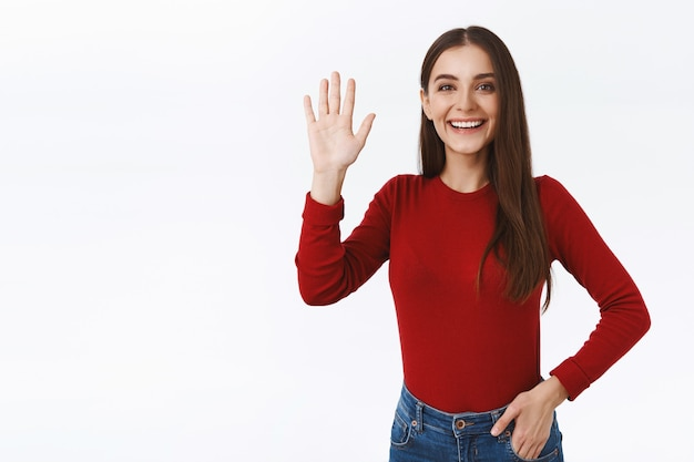 Vriendelijk, extravert en sociaal mooi brunette meisje in rode trui, verheugd om vriend te begroeten, hand op te steken, vreugdevol te zwaaien, iemand welkom te heten, hallo of hallo te zeggen, stand witte achtergrond