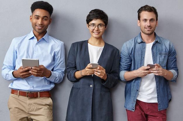 Vriendelijk gemengd raceteam van bedrijfsmedewerkers werkt met moderne technologieën