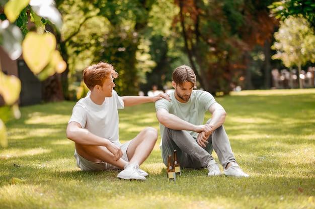 Vriendelijk gesprek. twee serieuze jongens in casual lichte kleding met flessen zitten en praten op groen gazon op zonnige dag