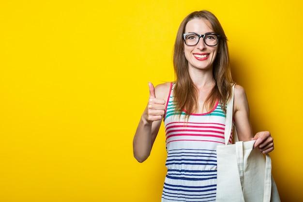 Vriendelijk glimlachend jong meisje in een gestreepte jurk en bril, met een linnen tas en een duim omhoog gebaar, klasse op een gele achtergrond.