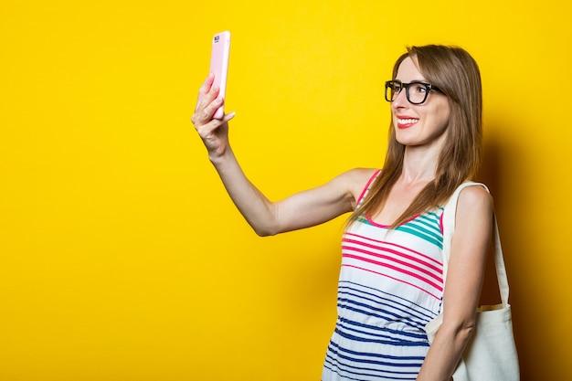 Vriendelijk glimlachend jong meisje met een telefoon en chatten op een gele achtergrond.