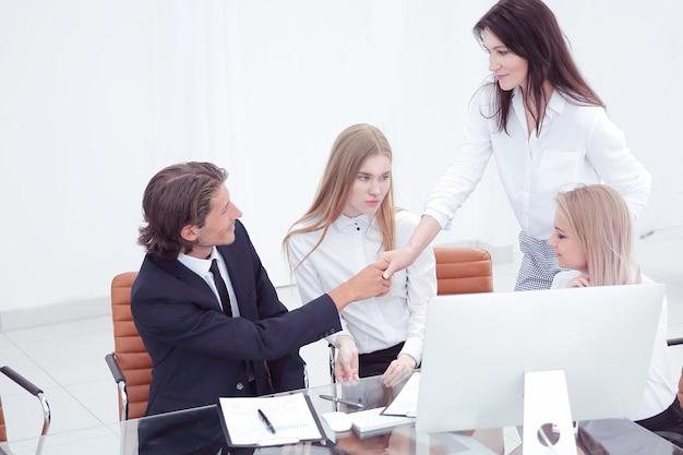 Vriendelijk glimlachende zakenman en onderneemsterhandshaking over het bureau