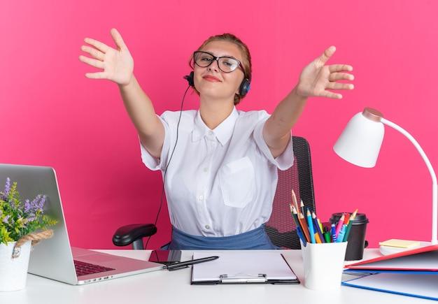 Vriendelijk jong blond callcentermeisje met een headset en een bril die aan het bureau zit met uitrustingsstukken die een welkomstgebaar doen