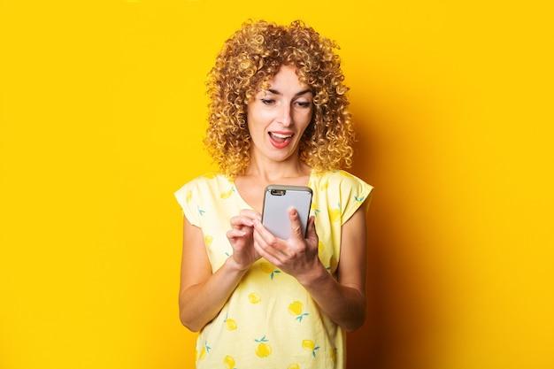 Vriendelijk jong krullend meisje kijkt naar de telefoon op een gele achtergrond.