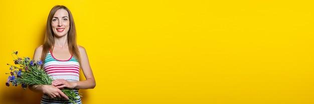 Vriendelijk jong meisje glimlachend met een boeket van wilde bloemen op een gele achtergrond. banier.