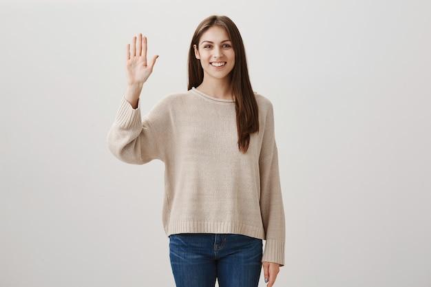 Vriendelijk kaukasisch meisje dat hallo zegt, hand in hallo gebaar zwaait, vrienden groet