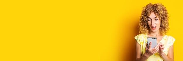 Vriendelijk krullend meisje kijkt naar de telefoon op een gele ondergrond