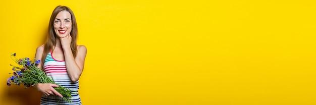 Vriendelijk lachend jong meisje in een gestreepte jurk met wilde bloemen op een gele achtergrond. banier.