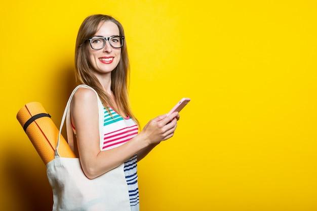 Vriendelijk lachend jong meisje met een telefoon, een tas met een yogamat op een schouder op een gele achtergrond.