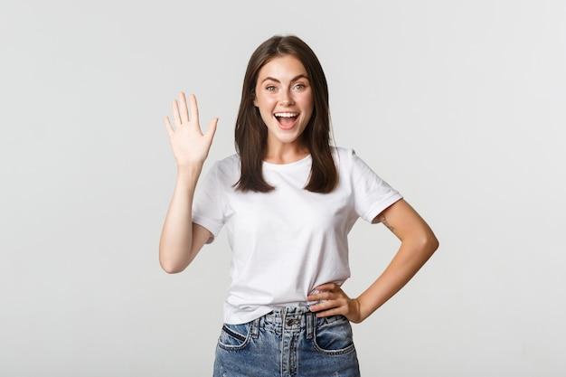 Vriendelijk lachend meisje zwaaiende hand om hallo te zeggen, iemand te begroeten.