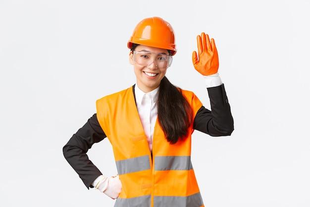 Vriendelijk lachende aziatische vrouwelijke bouwingenieur architect in veiligheidshelm handschoenen en bril wa...