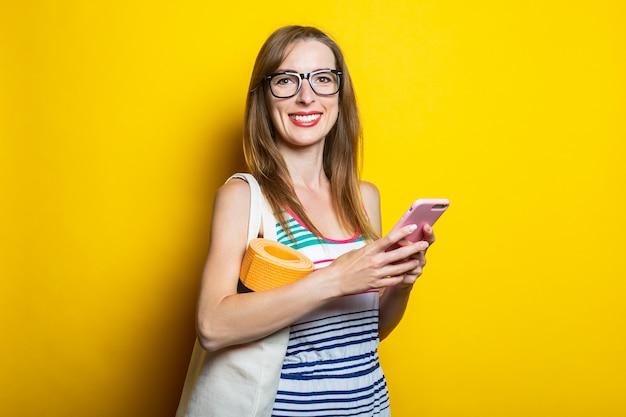 Vriendelijk lachende jonge vrouw met een telefoon op je schoudertas met yoga mat op een gele achtergrond.