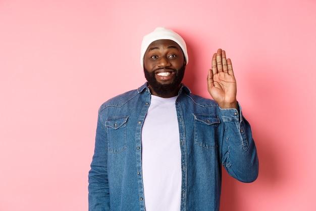 Vriendelijk lachende zwarte man die hallo zegt, met de hand zwaait, je groet, over roze achtergrond staat