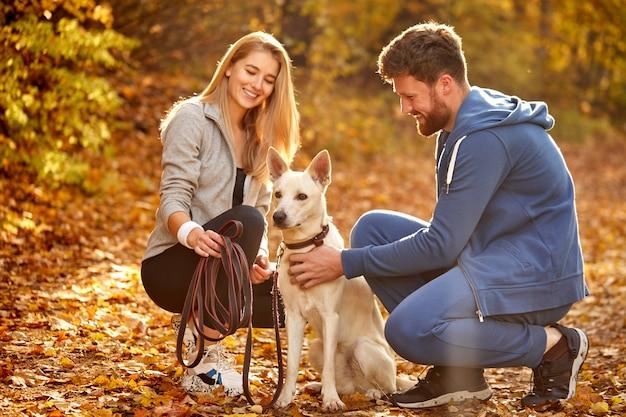 Vriendelijk leuk stel met witte hond in de natuur, zonnige herfstdag, spelen en aaien. perfect weer voor wandelingen