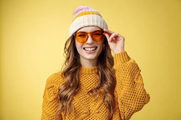 Vriendelijk ogend gelukkig uitgaande aantrekkelijk meisje lachen vreugdevol grappig interessant gesprek controleren zonnebril ontspannen skiresort plezier samen rusten vrienden, gele achtergrond