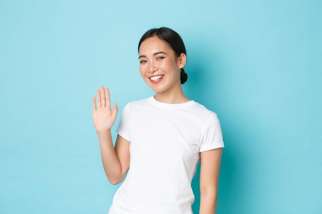Vriendelijk ogend vrolijk aziatisch meisje dat hallo zegt, nieuwe mensen in gezelschap groet, glimlachende koreaanse vrouwelijke zwaaiende hand om hallo te zeggen, iemand welkom heet, staande blauwe achtergrond vrolijk.