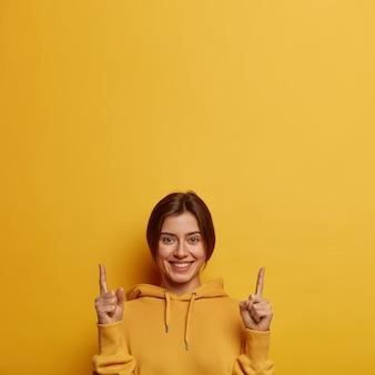 Vriendelijk ogende mooie vrouw toont promo met vreugde, wijst met beide wijsvingers naar boven, geeft aanbeveling of advies, draagt gele hoodie
