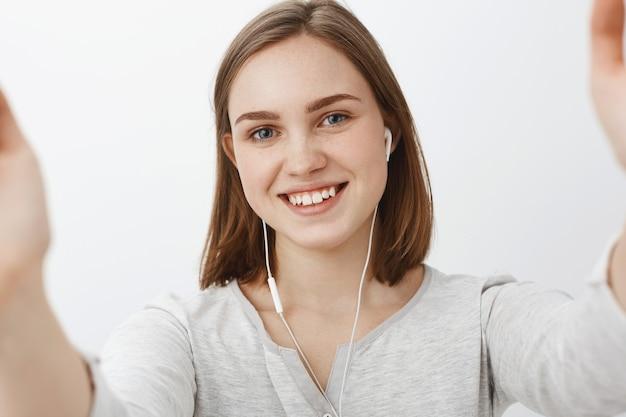 Vriendelijk ogende schattig en gelukkig jonge vrouw selfie te nemen