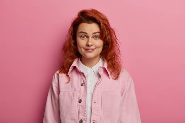 Vriendelijk ogende tedere meid heeft rood golvend haar, glimlacht met kuiltjes op de wangen, ziet er zorgeloos en ontspannen uit, is zelfverzekerd, geïsoleerd over roze ruimte. mensen