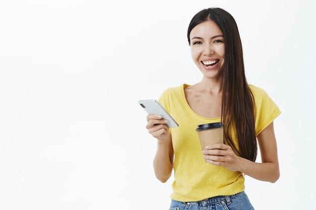 Vriendelijk ogende vrolijke en vermaakte aantrekkelijke europese vrouw met lang haar in trendy geel t-shirt met papieren kopje koffie