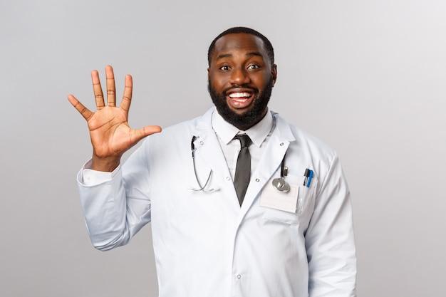 Vriendelijk ogende vrolijke knappe afro-amerikaanse arts, mannelijke arts die er vijf toont, vijfde nummer met hand, tevreden glimlacht, orde maakt of patiënten telt, werd genezen