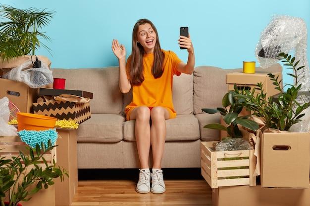 Vriendelijk ogende vrolijke vrouw maakt videogesprek