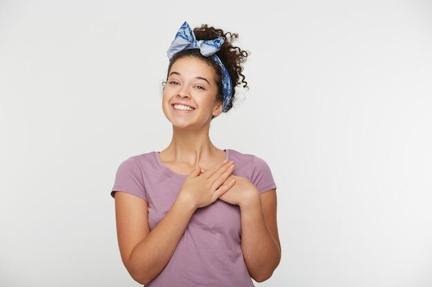 Vriendelijk ogende vrouw met krullend haar en hoofdband, houdt handen op de borst, handen in de buurt van het hart, ziet er vrolijk uit, lacht vrolijk