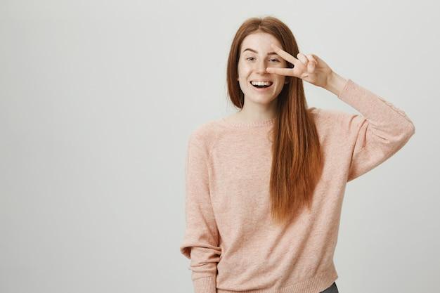 Vriendelijk optimistisch roodharigemeisje dat en vredesteken glimlacht toont