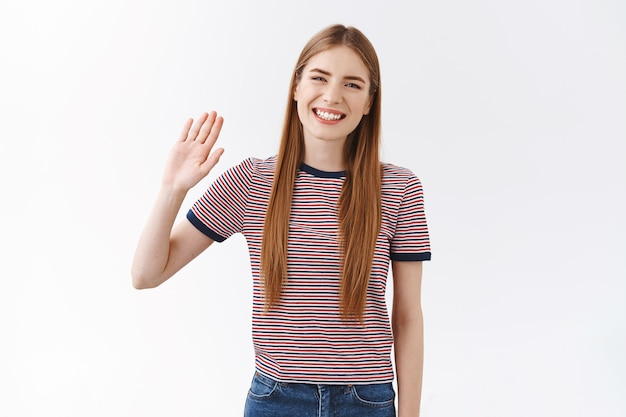 Vriendelijk positief, schattig jong kaukasisch meisje in gestreept t-shirt die palm opheft, zwaaiende hand zeg hallo, groet klasgenoot, glimlachend vrolijk en ontspannen, verwelkomende gasten, staande witte achtergrond