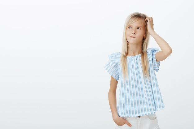 Vriendelijk schattig meisje dat een idee maakt hoe ze moeder kan opvrolijken. verward bezorgd klein kind met blond haar, krabbend hoofd en opkijkend tijdens het denken of plannen van de volgende stap, geen idee en onbewust