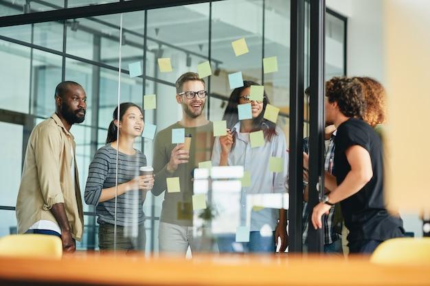 Vriendelijk team van collega's die samen achter glas staan en werken