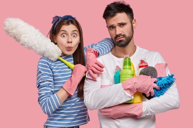Vriendelijk team van de schoonmaakdienst bezig met het schoonmaken van het huis, de muren in hun appartement wassen