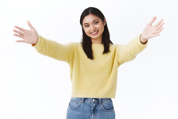 Vriendelijk teder aziatisch meisje met glanzende perfecte huid die je uitnodigt voor een knuffel, spreid de handen zijwaarts en reikt tot de camera om te knuffelen, omhels iemand die je dierbaar is, glimlachende gelukkige, witte muur