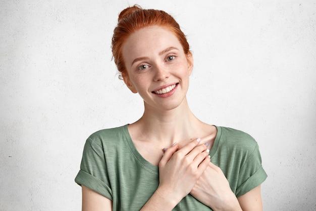 Vriendelijk tevreden mooi vrouwelijk model houdt de handen op het hart, dankbaar aan iemand, drukt haar vriendelijkheid of goede wil uit geïsoleerd op een witte betonnen muur.