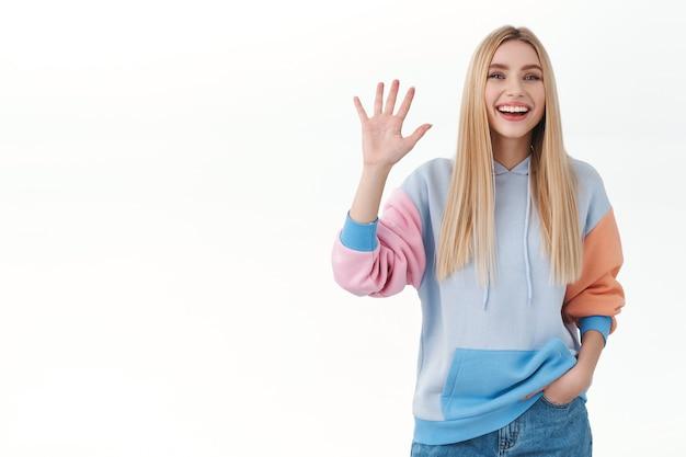 Vriendelijk vrolijk blond meisje dat breed lacht