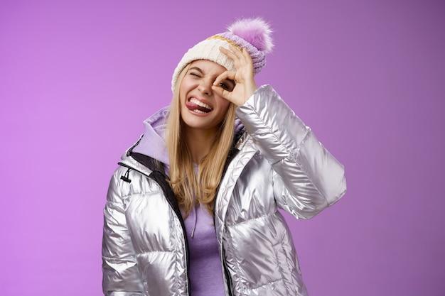 Vriendelijk, vrolijk kaukasisch blond meisje in hoed warme stijlvolle glanzende zilveren jas kantelen hoofd gelukkig tong glimlachen breed genieten van geweldige ski resort vakantie reizen winter, paarse achtergrond.