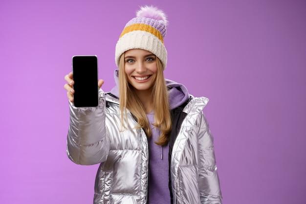Vriendelijk vrolijk zelfverzekerd blond meisje in zilveren stijlvolle winterjas hoed verlengen arm weergegeven: smartphone