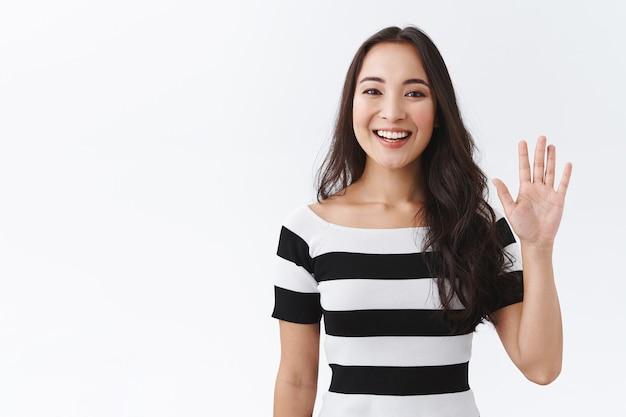 Vriendelijke, aangename en vrolijke oost-aziatische vrouw in gestreept t-shirt die palm opheft, hand groet, hallo of hallo zegt en lacht met vrolijke uitdrukking als gastvrije nieuwkomers, witte achtergrond