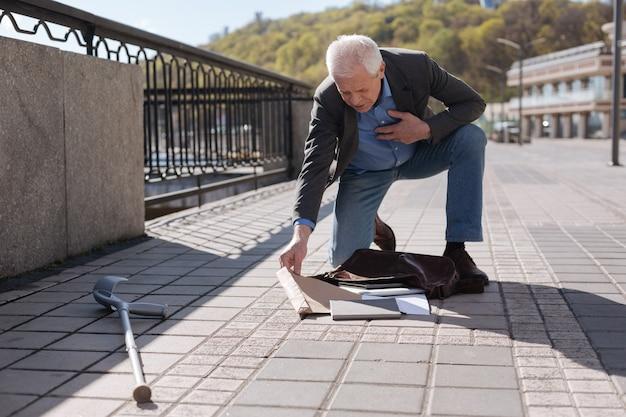 Vriendelijke, aangename verlegen gepensioneerde die zijn hand op de borst houdt en op de knie staat terwijl hij zijn tas inpakt