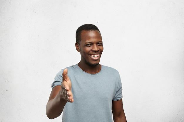 Vriendelijke aantrekkelijke afro-amerikaanse man die hand geeft voor handdruk als teken van begroeting, breed en oprecht glimlachend, kijkend erg blij om te zien persoon die hij ontmoet. menselijke emoties en gezichtsuitdrukkingen