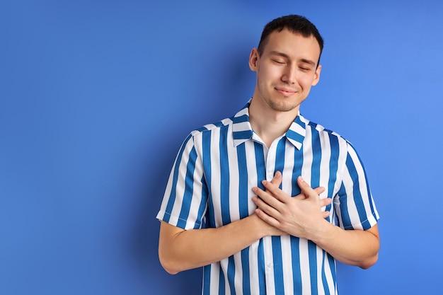 Vriendelijke aardige man met handen op de borst dankbaarheid uiten