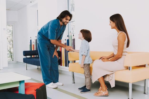 Vriendelijke arts handshaking met kid op kantoor