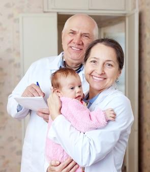 Vriendelijke artsen met kleine baby