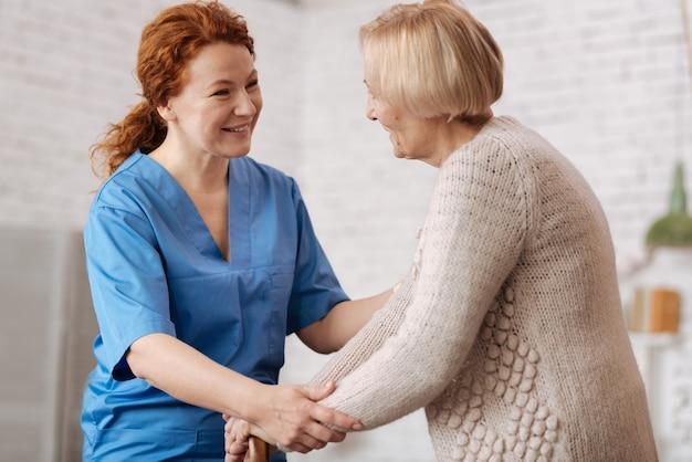 Vriendelijke assistent. aardige, zorgzame competente vrouw die de oudere dame vraagt of ze zich ok voelt terwijl ze haar wekelijks bezoekt voor algemeen onderzoek
