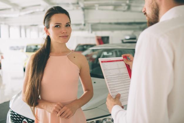 Vriendelijke autoverkoper die met een jonge vrouw spreekt en een nieuwe auto binnen toonzaal toont