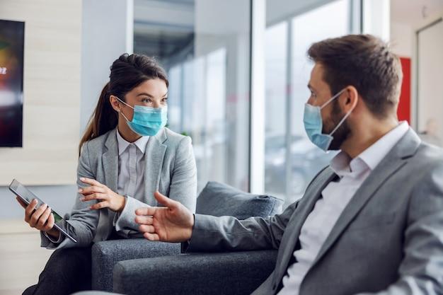 Vriendelijke autoverkoper met gezichtsmasker zittend met klant in autosalon, tablet vasthouden en praten over specificaties en prestaties van auto tijdens coronavirus.