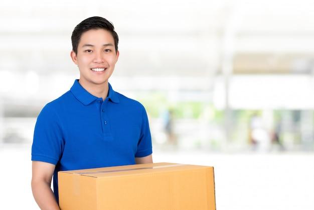 Vriendelijke aziatische bezorger in blauwe polo shirt met pakket doos