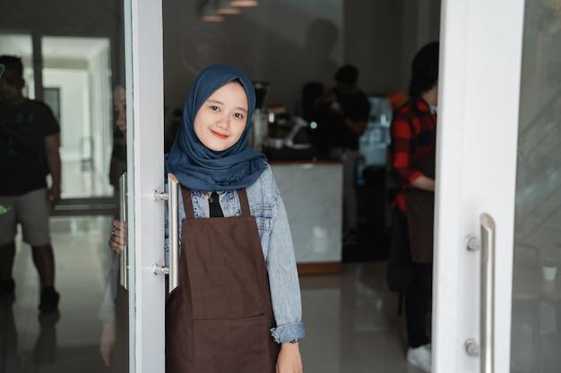 Vriendelijke aziatische mooie moslimvrouw gastvrije gast in de winkel