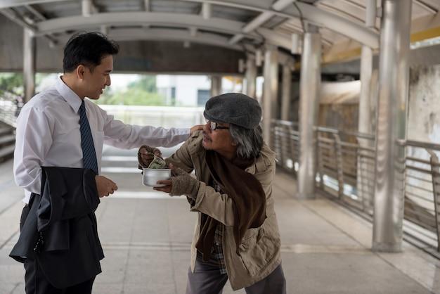 Vriendelijke aziatische zakenman geeft een dollarbiljet en vrolijkt oude bedelaar of dakloze man op tijdens stadswandeling. armoede en sociale kwestie concept. geef en deel met sympathie.
